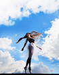 Ballerina dancing on the roof, clouds behind her