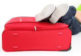 Legs of a young man lies on the red suitcase
