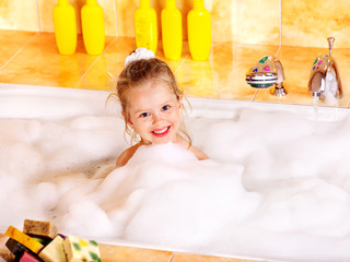 Child washing in bubble bath .