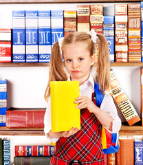 Child with book on bookshelf.