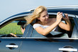 Attractive woman photographing from car window
