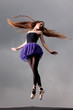 Ballerina dancing on the roof, stormy clouds behin her