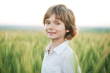Joyful boy against a wheat field