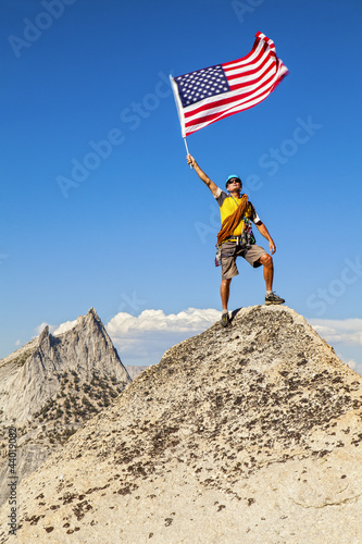 Climber waves flag on mountain peak.