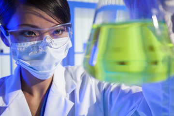 Chinese Female Woman Scientist With Green Flask In Laboratory