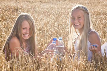 Zwei fröhliche durstige Mädchen im Getreidefeld