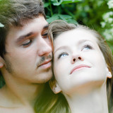 Young happy couple embracing tenderly among green leaves poster