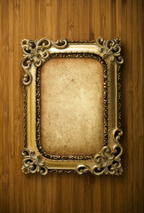 Gold frame with old paper on wood background