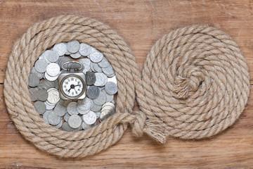 Rope frame, vintage clock, antique coins, on oak wood texture
