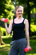 Woman working out with dumbbells in the park