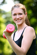 Beautiful woman with pink dumbbell in the park