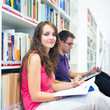 Two college students in library (color toned image; shallow DOF)