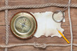 Compass, burnt paper, pencil, magnifying glass and rope on wood