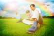 Adult man and his little son sitting on a grass at park and havi