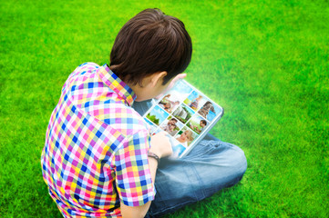 Little boy sitting on grass and using tablet computer to watch o