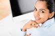 Closeup gorgeous Indian businesswoman at desk  smiling
