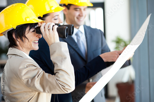 project manager looking at construction site with binoculars