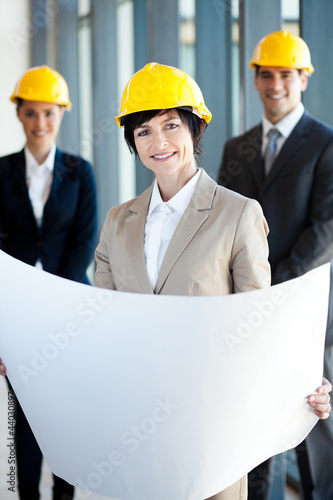 middle aged female architect holding blue print