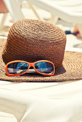 Straw hat with sunglasses on the longue