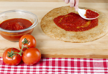 pizza dough with red sauce and tomatoes