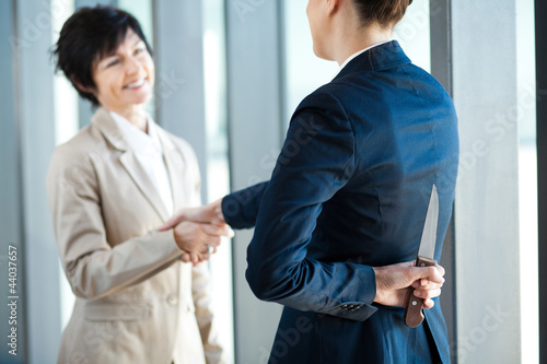 dangerous businesswoman holding knife behind her back