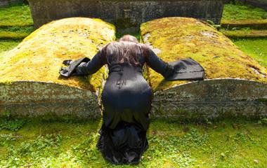 Eine schwarz gekleidete Frau kniet in einem alten Grabmal