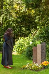 Eine schwarz gekleidete Frau betrachtet eine Gedenkstätte auf e