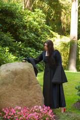 Eine schwarz gekleidete Frau legt einen Stein zu anderen Steinen
