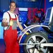 Master mechanic in a garage shows  thumb up for tyre fitting