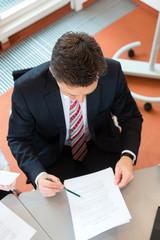Geschäftsmann sitzt im Büro an einem Schreibtisch