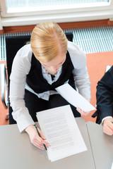 Eine Geschäftsfrau sitzt im Büro an einem Schreibtisch