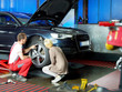 Female customer and mechanic checking the tyre of her car