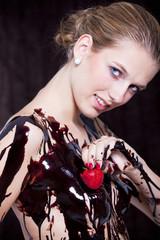 junge Frau spielt mit Erdbeere an der Brust voller Schokolade