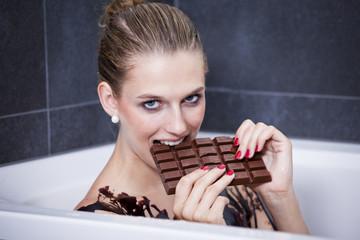 Frau isst Schokolade in der Badewanne