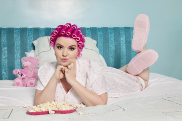 Portrait of young woman lying on bed with popcorn