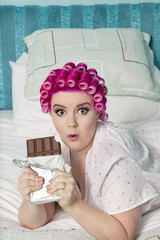 Portrait of shocked woman lying on bed with chocolate bar