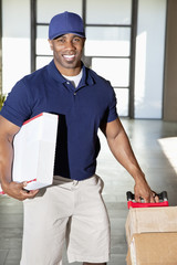 Portrait of a happy African American man carrying delivery boxes