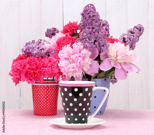 spring flowers and cup on table on white wooden background