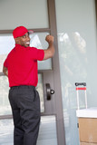 Young delivery man with packages looking back while knocking on door