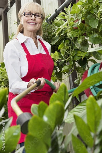 Portrait of a senior female gardener spraying pesticide on plants in botanical garden