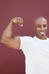 Portrait of an African American male flexing muscles over colored background