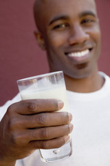 Close-up of young man holding milk glass