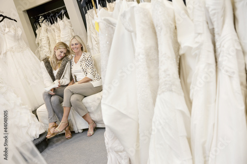 Happy mother and daughter sitting together on sofa in bridal boutique