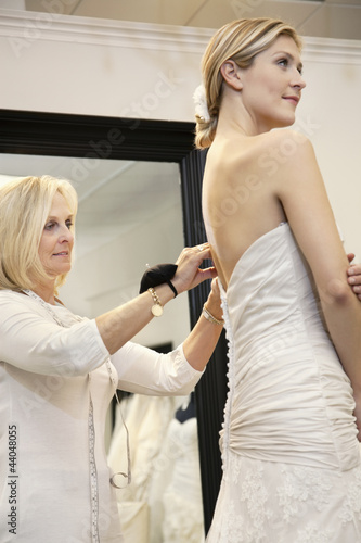 Beautiful woman dressed up in wedding dress while senior owner helping in bridal store