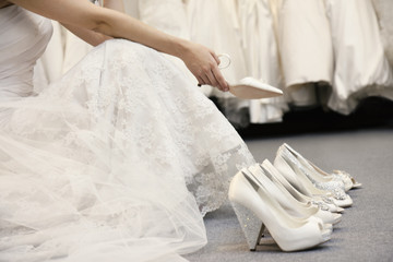 Low section of woman sitting with variety of footwear in bridal boutique