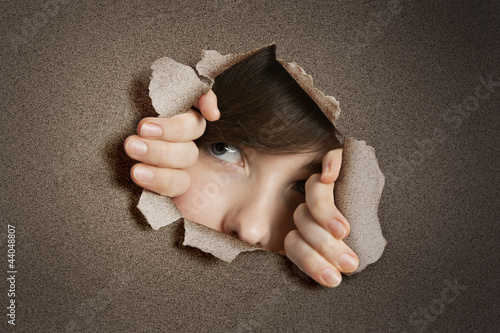 Young Middle eastern woman peeking from ripped white paper hole