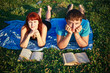 Two students read textbook against summer nature.