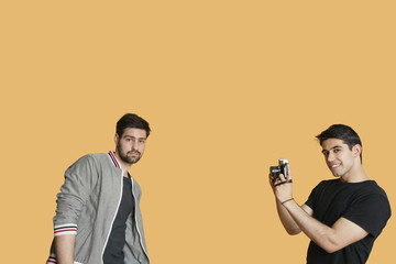 Portrait of young man photographing friend over colored background