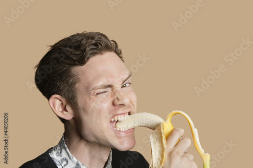 Portrait of a mid adult man winking while biting banana over colored background