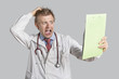 Male doctor terrified looking at medical reports over gray background